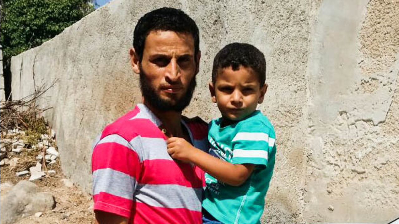 Eisa and his son, in front of his home.