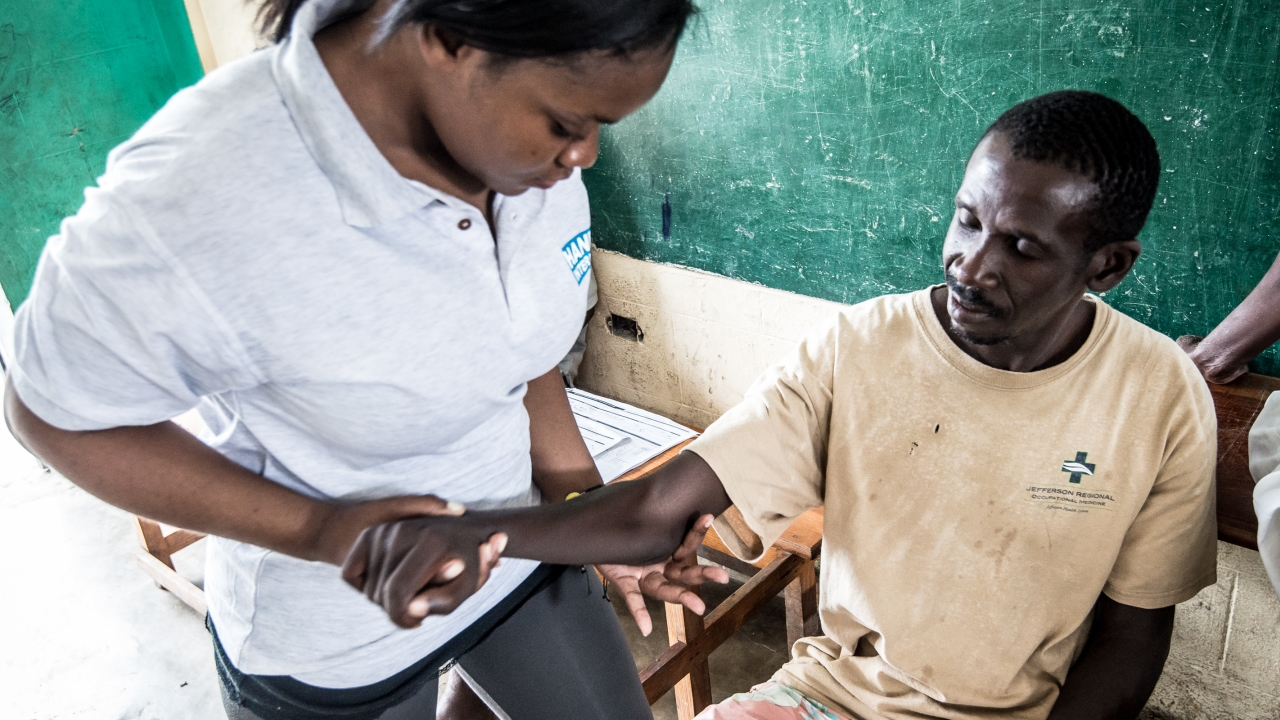 A man suffering hemiplegia after the disaster,receiving physiotherapy care from a physiotherapist of Handicap International.