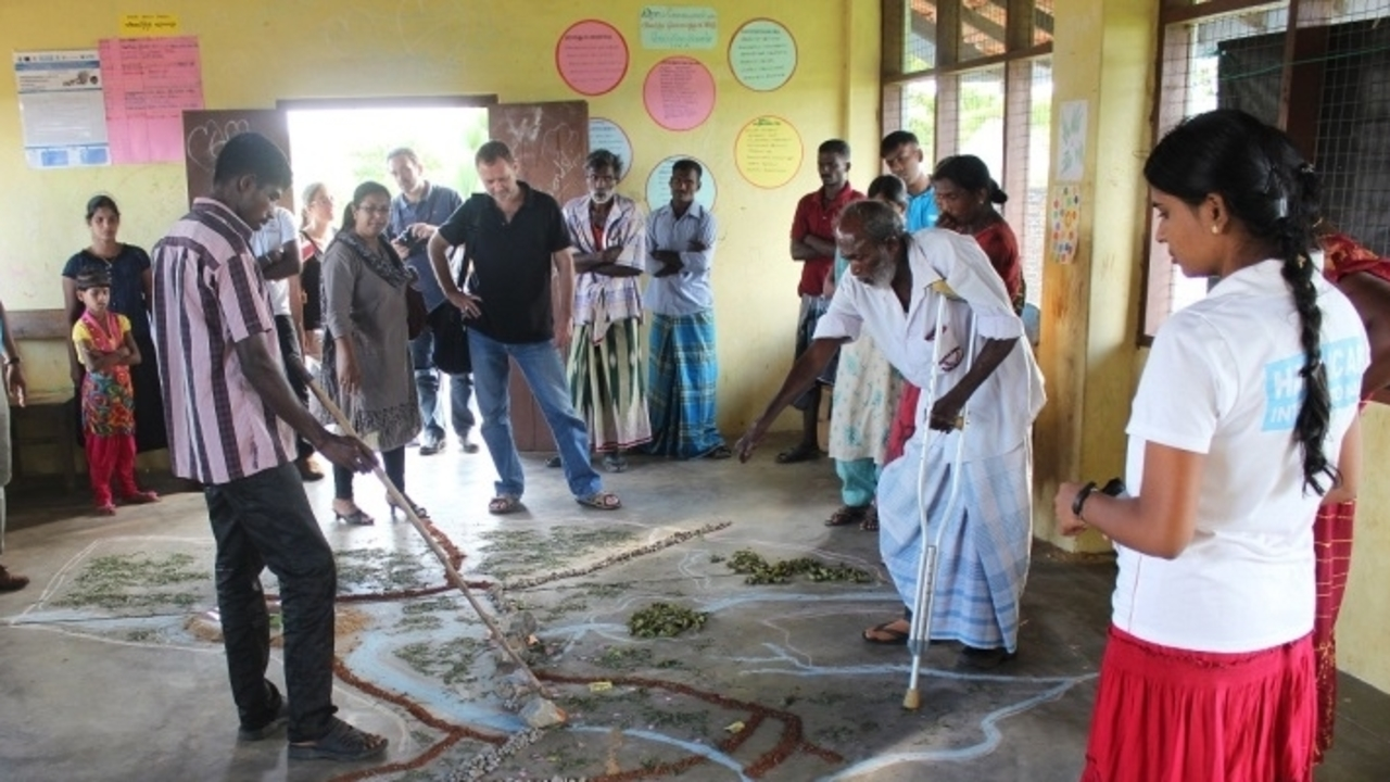 Villages in the Batticaloa region of Sri Lanka meet to draw up an emergency evacuation plan. They have drawn a map of the village on the ground.