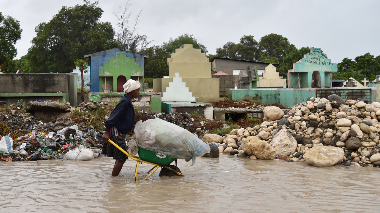 « A woman pushes a wheelbarrow while walking in a partially flooded street, in the Haitian capital, Port-au-Prince, on October 4, 2016.
