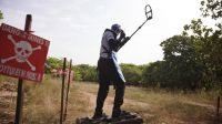 Deminer Souleye using matramine and metal detector on a test field at the entrance of Diagnon Village, East of Ziguinchor. Matramines are a security tool: they are air-blown shoes that spread the weight of deminer body then preventing to trigger landmine; }}
