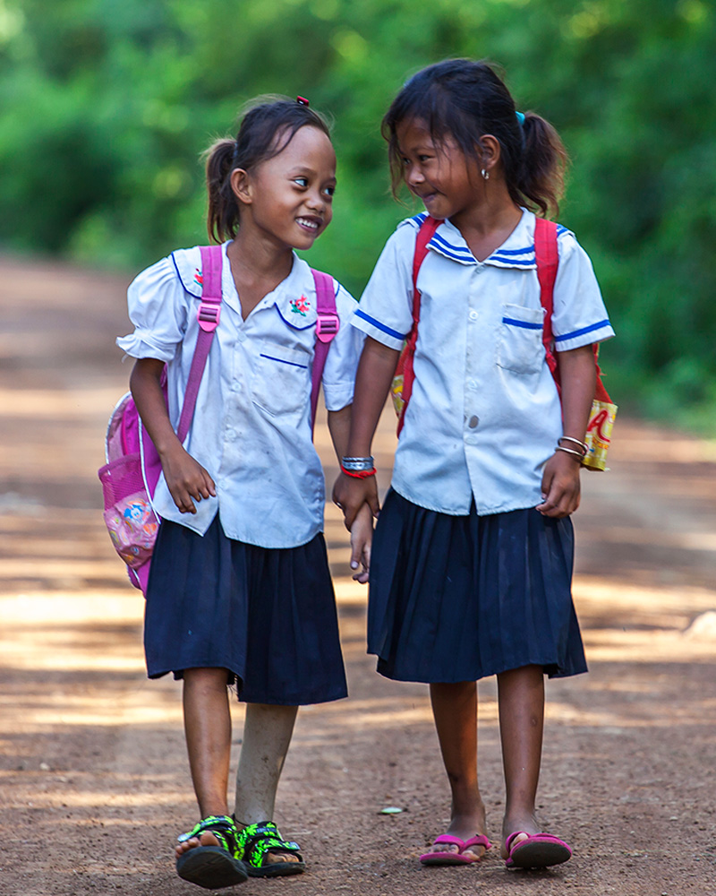 Channa, 7 years old, with a classmate on the way to school
