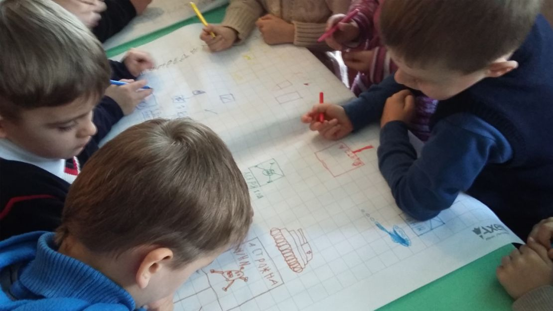 Children drawing dangerous situations during a mine risk education session in Ukraine.
