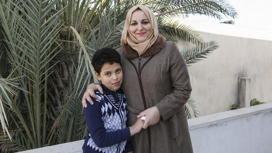 Suha and her son Mahmoud outside the school supported by HI