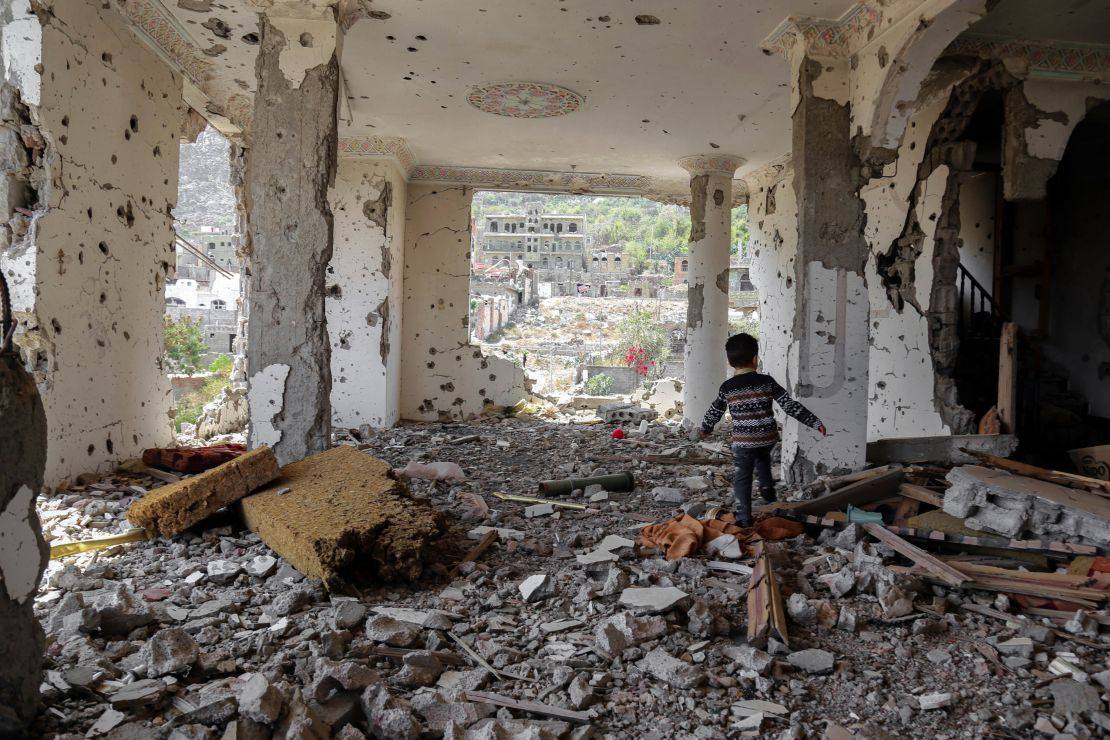 Yemen, conflict. A Yemeni child walks through the rubble of a building that was destroyed during an air strike in the southern Yemen town of Taez. March 2018.