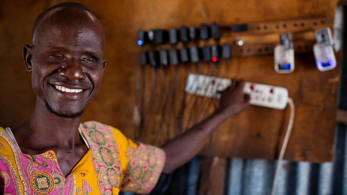 Blind Ali charges phones in the shop he owns with his wife Abiba, who is also blind, in Kakuma Town, Kenya. Both Ali and Abiba are from Kakuma and have received support for their shop from Humanity & Inclusion and other NGOs after NGO's arrived to support the influx of refugees.